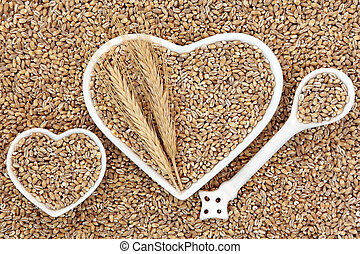 Pearl barley health food in heart shaped bowls and porcelain spoon forming an abstract background.
