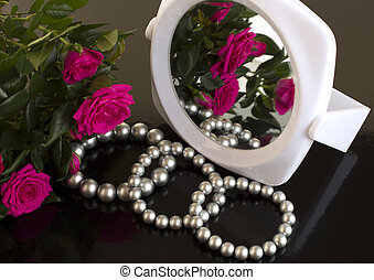 pearl bracelets, bouquet of roses and a mirror