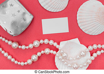 Pearl jewelry and blank card on pink background