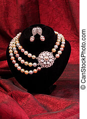 Pearl necklace and earring on a red background