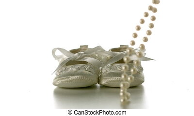 Pearl necklace falling onto baby shoes in slow motion