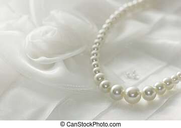 Pearl necklace on lace background, selected focus.