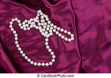 Pearl necklace on purple satin fabric background