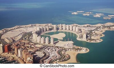 Passenger window view of Pearl Qatar, an artificial island, with its modern, highrise architecture, from a commercial airliner. FullHD footage