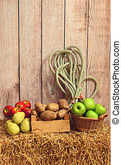 pears apples potatoes on hay bale with rope