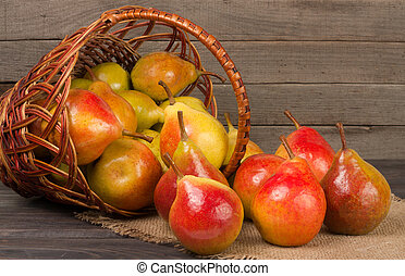 pears in a wicker basket on wooden table with napkin of burlap