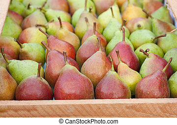 Pears in a wooden box as background