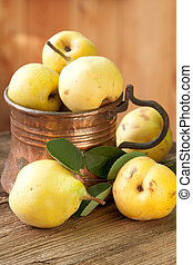 pears in copper jug on wooden background