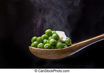 Peas on spoon topped with butter.