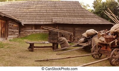 Peasant countryman stuff beside his wooden house. Rustic wagons, bags, barrel etc. Medieval yard.