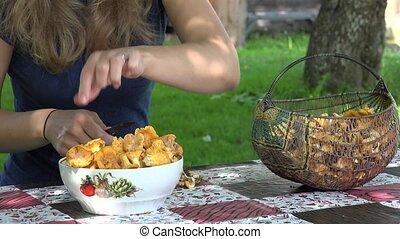 peasant girl clean chanterelle mushrooms on table. 4K