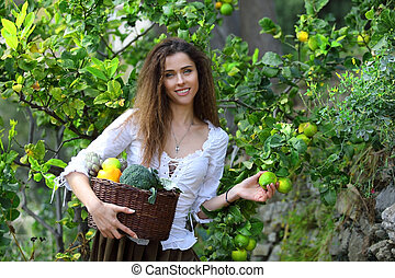 Peasant girl picking some ripe lemons from a tree