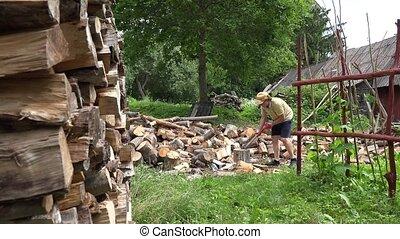 Peasant man in shorts prepare firewood. 4K - Strong peasant...