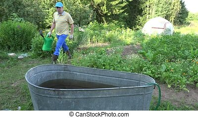 Peasant man with watering can draw water from water barrel in garden. 4K