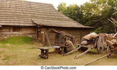 Peasant yard with carts and bags. Rustic medieval life. Cabin house in a forest.