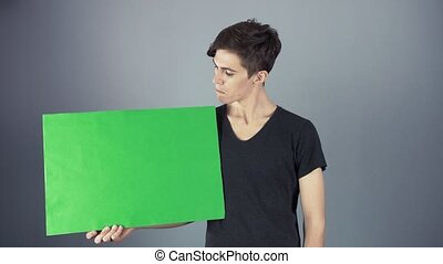 Peased Young man in black shirt holding green key sheet poster gray background