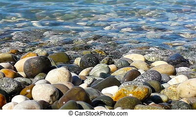 Pebble and sea water at sunny summer day, close up view -...