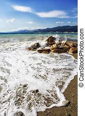Pebble beach in the resort of Kabardinka, Krasnodar region, Black sea. Waves and surf on a pebble beach. On the horizon of the mountain - Markoth ridge.