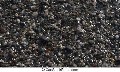 Pebble beach sea shore, transparent crystal shallow water...