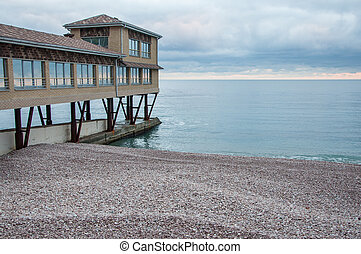 pebble beach with a house on the pier at sunset