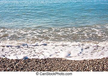 Pebble beach with sea waves