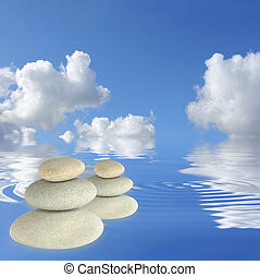 Abstract of two stacks of gray pebbles floating on rippled water set against a blue sky with clouds.