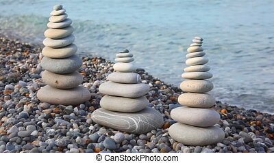 pebble stack on the stone seashore, sea in background