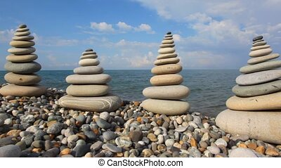 pebble stack on the stone seashore, sea and sky in background