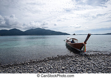 Pebble stone on the beach with boat