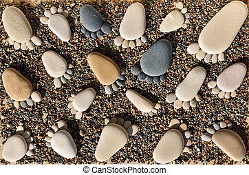 Pebble stones arranged like footprints on the beach. Family ...