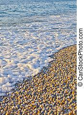 Pebble stones by the sea. Waves of blue Tyrrhenian sea.