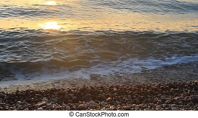 Pebbles and sea splashing at sunrise in Kemer, Turkey