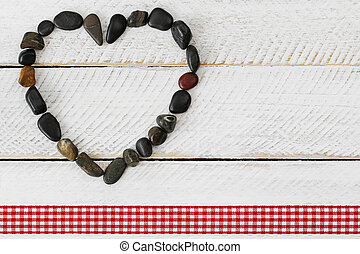 Pebbles arranged as a heart on white wooden background with ...