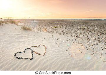 Pebbles arranged in shape of two hearts on sand beach...