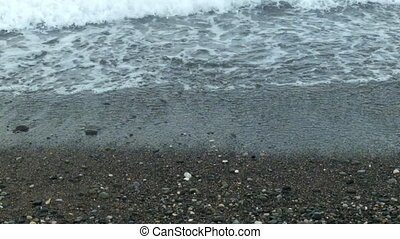 Pebbles coast and waves in cloudy day