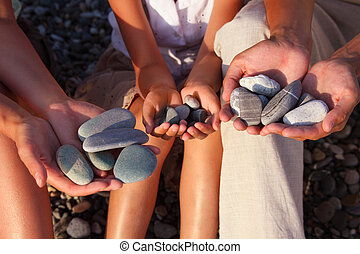 pebbles in family with girl hands