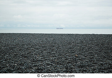 Pebbles on a beach leading to a silver sea.