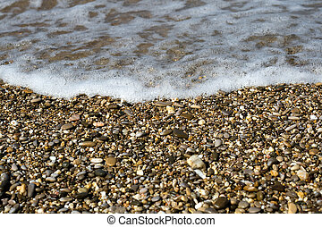 Pebbles on beach with sea wave