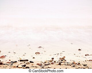 Pebbles on sandy beach against foamy sea water. Natural romantic offshore