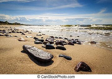 Pebbles on the beach shining in sun