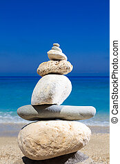 Pebbles stack balance over blue ionian sea