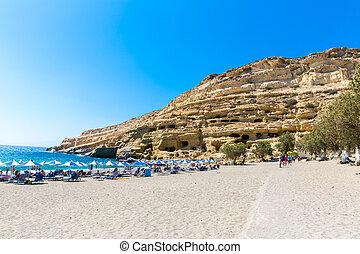 Pebbly beach Matala, Greece Crete. Matala has become famous for artificial Neolithic caves, carved in limestone rocks. During the 70's the caves were hosting an international hippie community