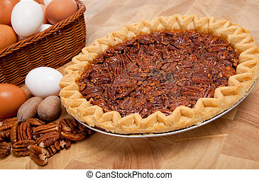 Pecan pie with ingredients on a cutting board