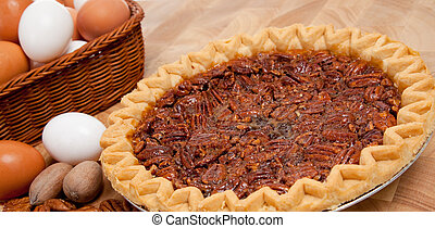 Pecan pie with ingredients on a wooden cutting board