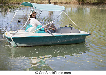 Pedal boat ride in the lake - Happy young woman having fun...