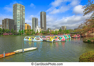 Pedal boats and tokyo cityscape on background on Shinobazu Pond in Ueno Park, a public park next to Ueno Station in central Tokyo. Ueno Park is considered the best in Tokyo for cherry blossoms.