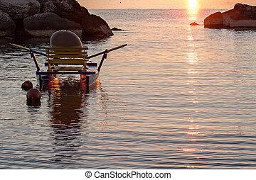 Pedalo moored in the sea at sunrise