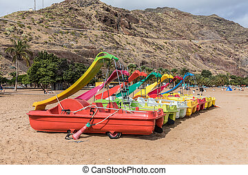 Pedalo with playground slide on the beach