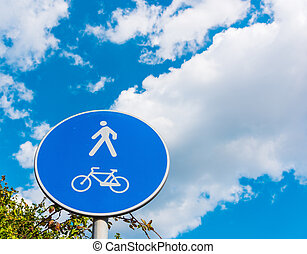 Pedestrian and bike sign under a cloudy sky
