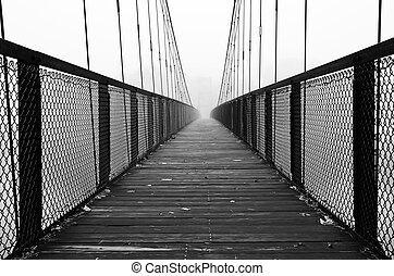 Pedestrian bridge across a river on a foggy autumn day